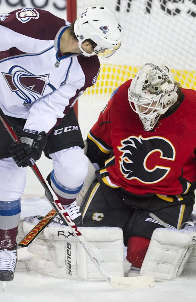 Colorado Avalanche's Maxime Talbot, left, gets his skate caught in the pads of Calgary Flames goalie Karry Ram during the first period of an NHL hockey game, Friday, Dec. 6, 2013 in Calgary, Alberta