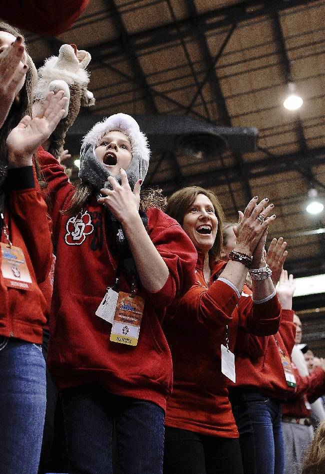 South Dakota fans from left, Morgan Herbster, 15, her sister, Leah Herbster, 9, and their mother, Kelly Herbster, cheer for their team during the first half between South Dakota and Denver an NCAA college basketball game for the championship of the Summit League women's tournament Tuesday, March 11, 2014, in Sioux Falls, S.D. South Dakota won 82-71