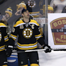 Boston Bruins defensemen Zdeno Chara, right, and Johnny Boychuk wear Boston Fire Department caps, honoring two Boston firefighters who died Wednesday after becoming trapped in a basement in a brownstone apartment building, as the Bruins warmed up to face