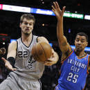 San Antonio Spurs forward Tiago Splitter, left, of Brazil, and Oklahoma City Thunder guard Thabo Sefolosha, of Switzerland, chase a rebound during the first half of an NBA basketball game, Saturday, Dec. 21, 2013, in San Antonio. (AP Photo/Darren Abate)
