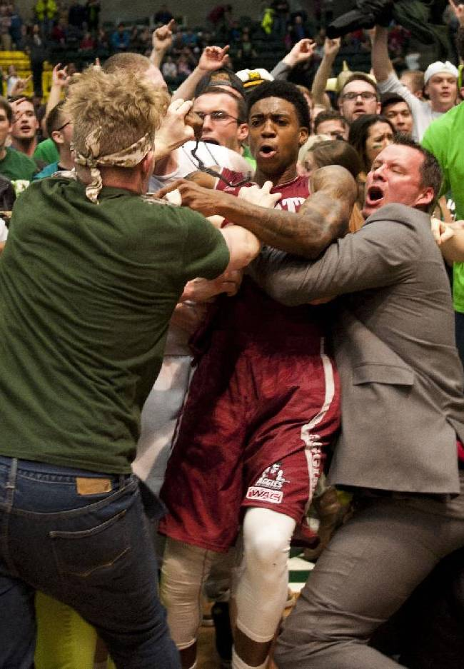 In this Thursday, Feb. 27, 2014 photo, New Mexico State's Daniel Mullings, at center in red and white jersey, is involved in a brawl involving players and fans who came onto the court when New Mexico State guard K.C. Ross-Miller hurled the ball at Utah Valley's Holton Hunsaker seconds after the Wolverines' 66-61 overtime victory against the Aggies in Orem, Utah