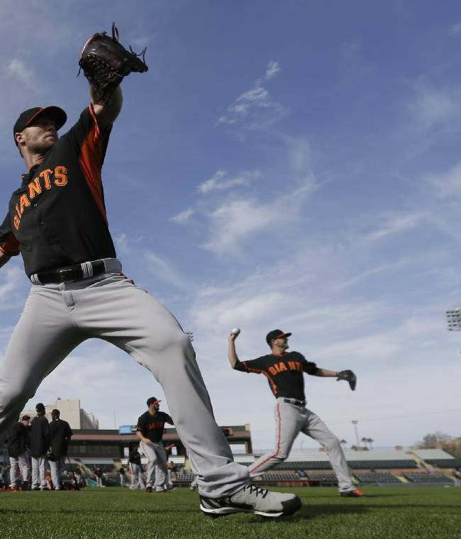 San Francisco Giants pitcher Hunter Strickland, left, and Giants invitee Chris Heston, right, warm up during spring training baseball practice on Sunday, Feb. 16, 2014, in Scottsdale, Ariz