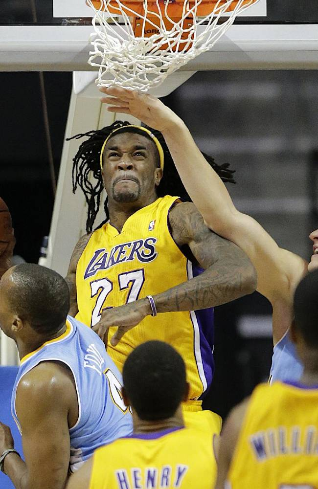Los Angeles Lakers' Jordan Hill, center, goes up for a basket against Denver Nuggets' Randy Foye, left, and Timofey Mozgov, right, of Russia, in the second half of an NBA preseason basketball game on Tuesday, Oct. 8, 2013, in Ontario, Calif. The Lakers won 90-88