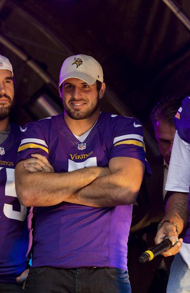 Minnesota Vikings' injured quarterback Christian Ponder, center, stands on stage flanked by his teammates, center John Sullivan, left, and defensive tackle Kevin Williams during an American football NFL fan rally event in Regent Street, central London, Saturday, Sept. 28, 2013.  The Minnesota Vikings are to play the Pittsburgh Steelers at Wembley stadium in London on Sunday, Sept. 29 in a regular season NFL game