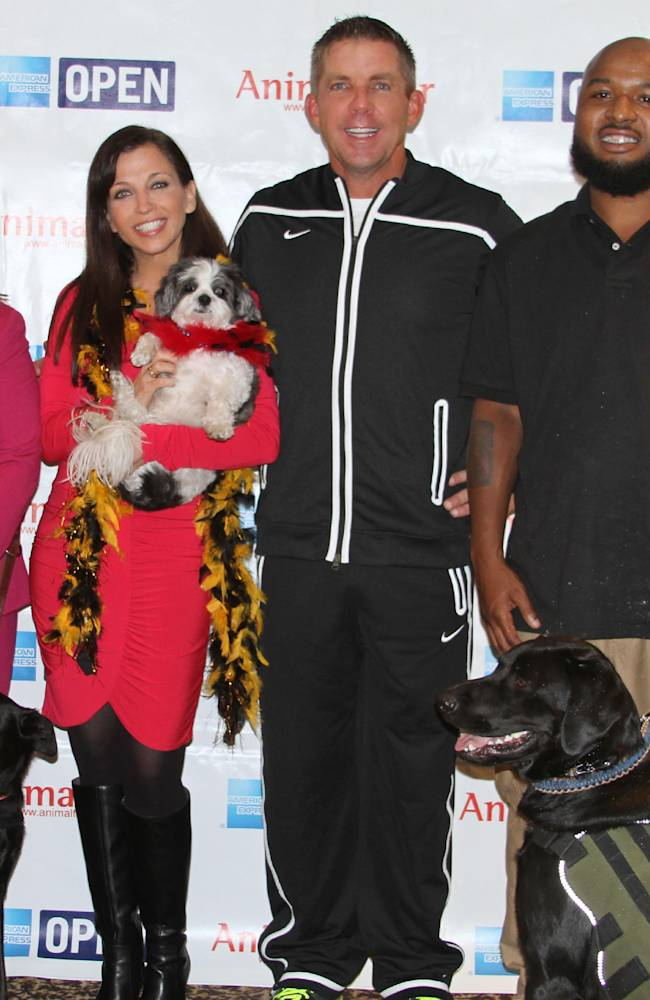 In this photo provided by Animal Fair Media, Inc., author and animal activist Wendy Diamond, center left, and New Orleans Saints coach Sean Payton, center right, join K9 for Warriors Graduates Army Sergeant Sheri Martinez and Lola, left, and Army Sergeant Chris Spikes with his new dog Seal, at the New Orleans stop of the