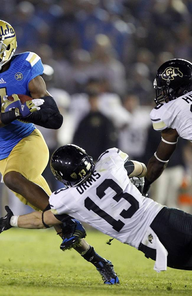 UCLA wide receiver Shaquelle Evans (1) cuts back on a 36-yard run after a catch as Colorado defensive backs Parker Orms (13) and Jeffrey Hall (16) attempt to make the stop in the second half of their NCAA college football game Saturday, Nov. 2, 2013, in Pasadena, Calif. UCLA won the game 45-23