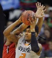 Oklahoma State forward Le'Bryan Nash (2) passes to a teammate while covered by Texas Tech forward Jordan Tolbert, back, during the first half of an NCAA college basketball game in the Big 12 men's tournament in Kansas City, Mo., Wednesday, March 12, 2014. (AP Photo/Orlin Wagner)