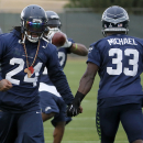 Seattle Seahawks' Marshawn Lynch (24) low-fives teammate Christine Michael (33) as they run drills during a team practice for NFL Super Bowl XLIX football game, Wednesday, Jan. 28, 2015, in Tempe, Ariz. The Seahawks play the New England Patriots in Super