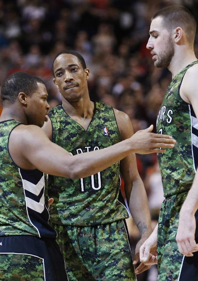 Toronto Raptors' Kyle Lowry, left, celebrates his 3-pointer against the Minnesota Timberwolves with teammates DeMar DeRozan, center, and Jonas Valanciunas during the second half of an NBA basketball game Friday, Jan. 17, 2014, in Toronto