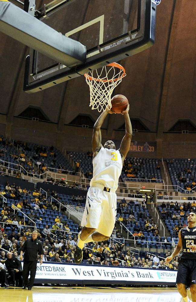 West Virginia's Juwan Staten dunks during the second half of an NCAA college basketball game against Mount St. Mary's in Morgantown, W.Va., Friday, Nov. 8, 2013. West Virginia won 77-62