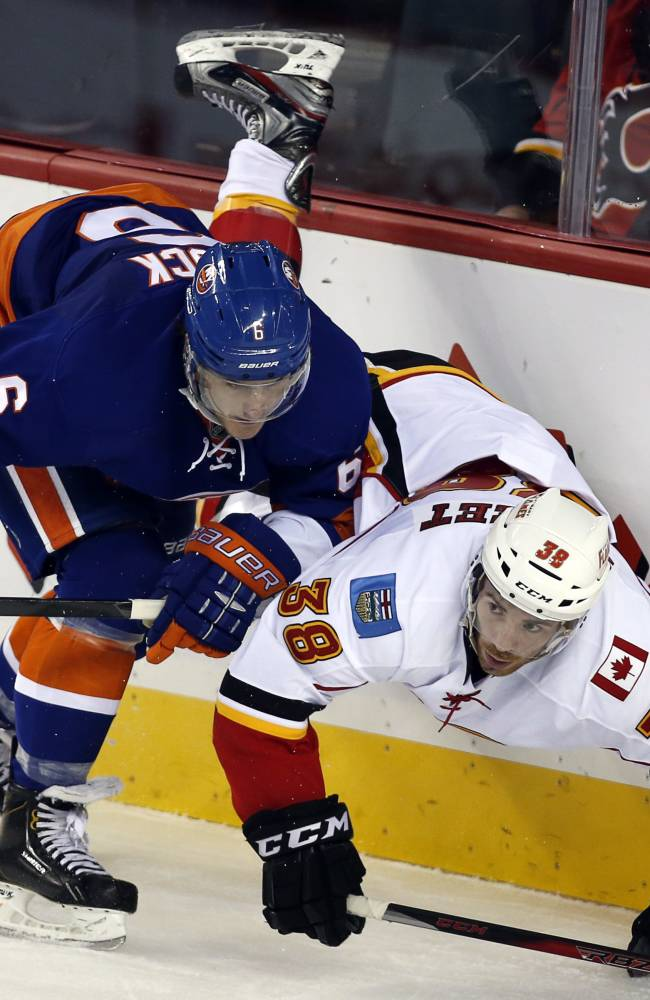 New York Islanders' Ryan Pulock, left, checks Calgary Flames' Ben Street during the third period of a preseason NHL hockey game Tuesday, Sept. 17, 2013, in Calgary, Alberta. Calgary won 5-3