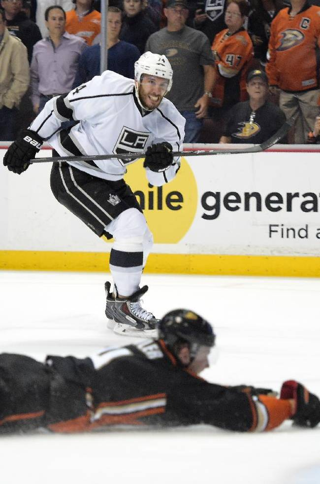 Los Angeles Kings left wing Dwight King, top, shoots and scores an empty net goal as Anaheim Ducks defenseman Cam Fowler dives in front during the third period in Game 2 of an NHL hockey second-round Stanley Cup playoff series, Monday, May 5, 2014, in Anaheim, Calif. The Kings won 3-1
