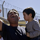 Daniel Rodriguez holds three-year-old Matthew Huert as he leads a chant for members of the group Border Dreamers and other supporters of an open border policy who marched to the United States border Monday, March 10, 2014, in Tijuana, Mexico The Associate