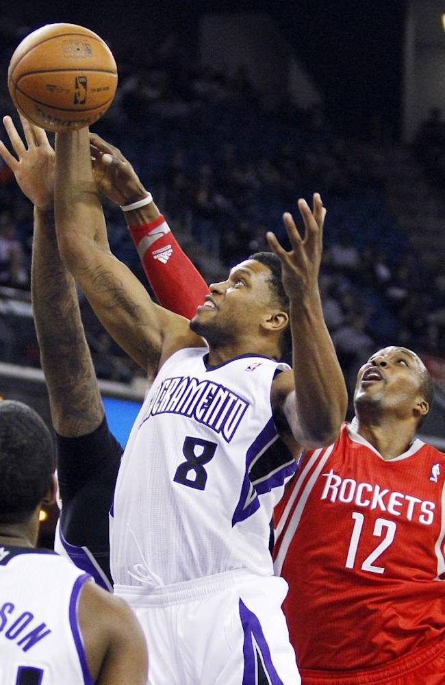 Sacramento Kings forward Rudy Gay (8) brings down a rebound against Houston Rockets forward Dwight Howard (12) during the first half of an NBA basketball game in Sacramento, Calif., Sunday, Dec. 15, 2013