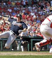 Atlanta Braves' Elliot Johnson, left, scores on a sacrifice fly by Gerald Laird as St. Louis Cardinals catcher Yadier Molina, right, looks for the throw during the eighth inning of a baseball game Sunday, Aug. 25, 2013, in St. Louis. (AP Photo/Jeff Roberson)
