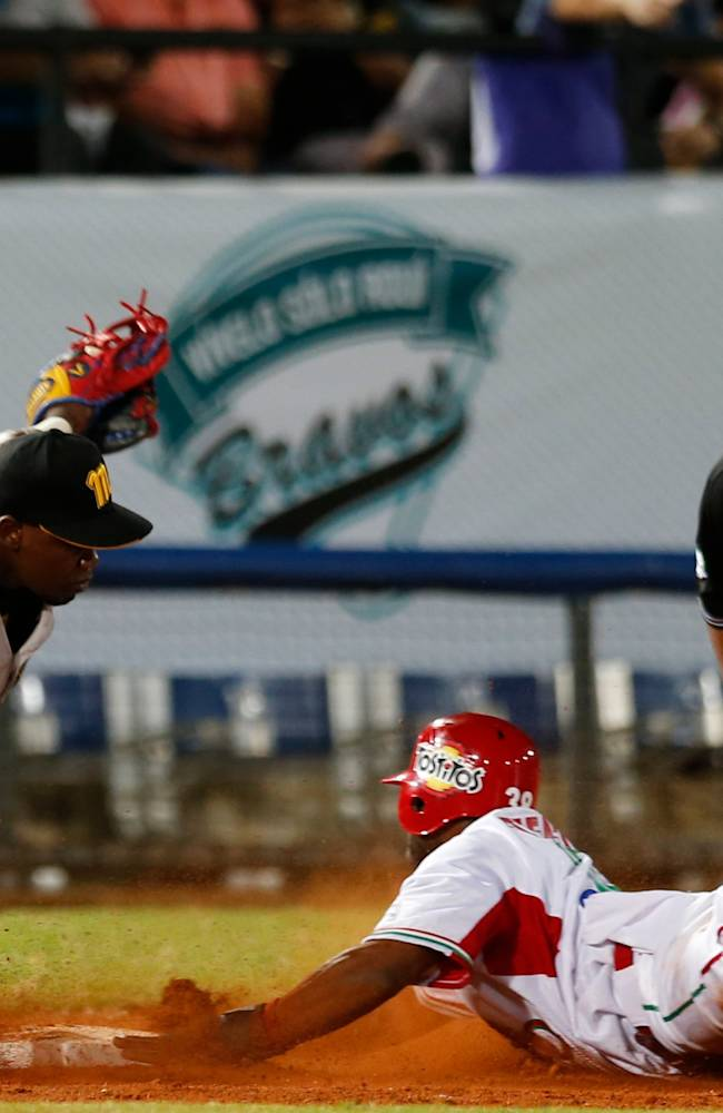 Venezuela's infielder Adonis Garcia, left, is tagged out at third base by Mexico's infielder Zelous Wheeler during a Caribbean Series baseball game in Porlamar, Venezuela, Monday, Feb. 3, 2014