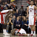 Toronto Raptors forward Amir Johnson, left, and guard Greivis Vasquez (21) stand near as guard Kyle Lowry lies on the floor injured during the second half of an NBA basketball game against the Phoenix Suns in Toronto on Sunday, March 16, 2014 The Associat