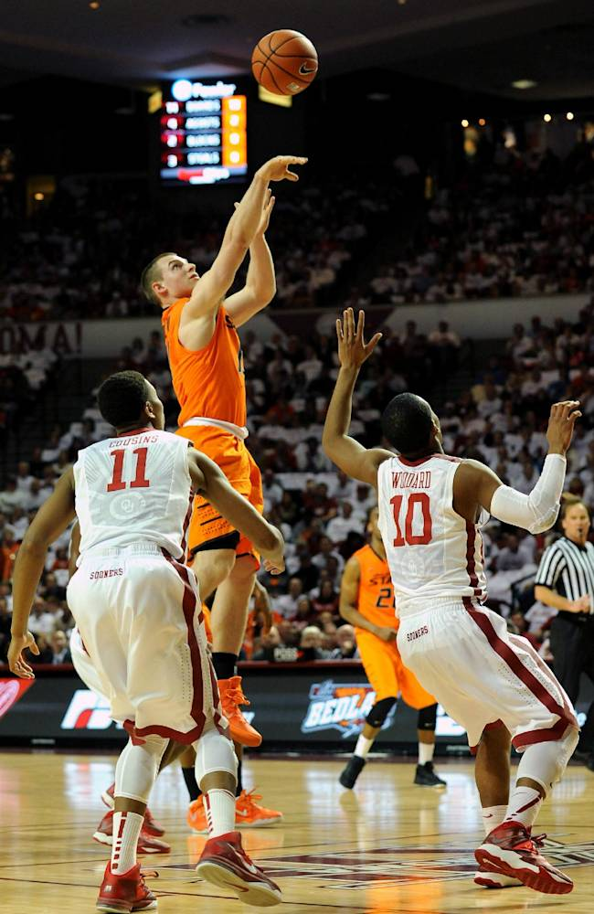 Oklahoma guard Isaiah Cousins, left, and Jordan Woodard watch as Oklahoma State guard Phil Forte, center, takes a shot during the first half of an NCAA college basketball game in Norman, Okla., Monday, Jan. 27, 2014. Forte scored 20 points in the 76-88 loss to rival Oklahoma