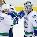 Vancouver Canucks goalie Eddie Lack (31) celebrates with Brad Richardson (15), who had two goals in a 3-0 shutout win over the Pittsburgh Penguins in an NHL hockey game in Pittsburgh Thursday, Dec. 4, 2014 The Associated Press