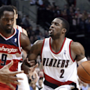 Portland Trail Blazers guard Wesley Matthews, right, looks to shoot as Washington Wizards forward Martell Webster holds on to his arm during the second half of an NBA basketball game in Portland, Ore., Thursday, March 20, 2014. Matthews led the Trail Blaz