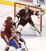 Phoenix Coyotes' Mike Smith (41) makes a glove save on a shot by New York Islanders' Eric Boulton, right, as Coyotes' Michael Stone, left, defends during the second period of an NHL hockey game Thursday, Dec. 12, 2013, in Glendale, Ariz. (AP Photo/Ross D. Franklin)