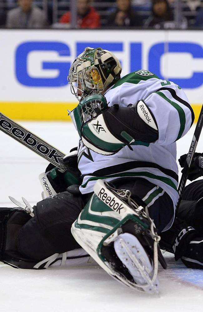 Dallas Stars goalie Dan Ellis, left, stops a shot as he falls over Los Angeles Kings right wing Dustin Brown during the second period of their NHL hockey game, Saturday, Oct. 19, 2013, in Los Angeles, Calif