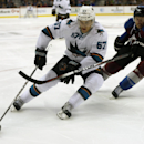 San Jose Sharks center Tommy Wingels, left, works the puck inside for shot past Colorado Avalanche defenseman Erik Johnson in the overtime period of the Sharks' 3-2 shootout victory in an NHL hockey game in Denver on Tuesday, Oct. 28, 2014 The Associated