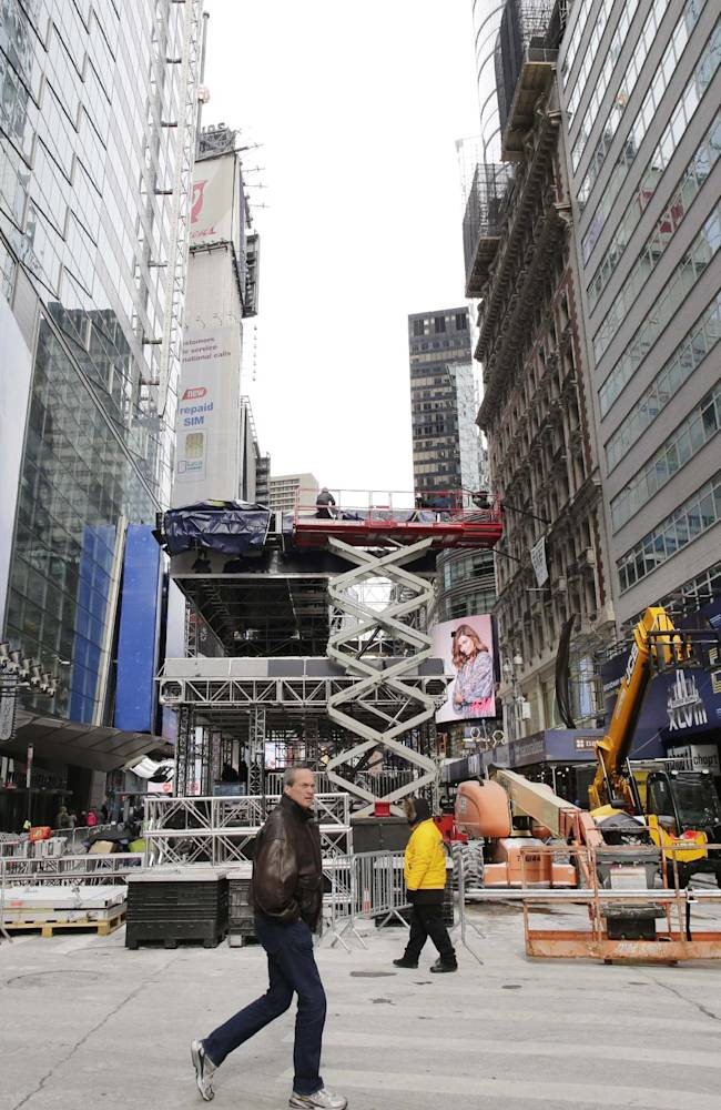 A pedestrian passes a soundstage under construction in New York's Times Square, Sunday, Jan. 26, 2014. A dozen blocks of Broadway, in the heart of Manhattan, will close to traffic for four days so the NFL can host a Super Bowl festival. The championship football game between the Denver Broncos and Seattle Seahawks is Sunday, Feb. 3 in East Rutherford, N.J