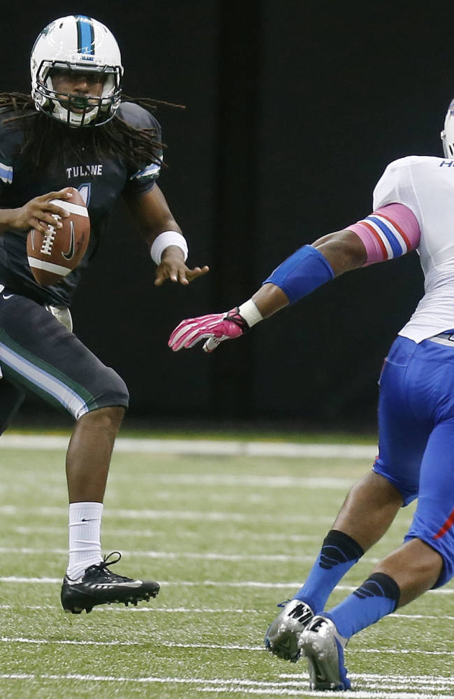 Tulane Green Wave quarterback Devin Powell, left, rolls away from Tulsa Golden Hurricane defensive end Chris Hummingbird in the second half of an NCAA college football game in New Orleans, Saturday, Oct. 26, 2013. Tulane won 14-4