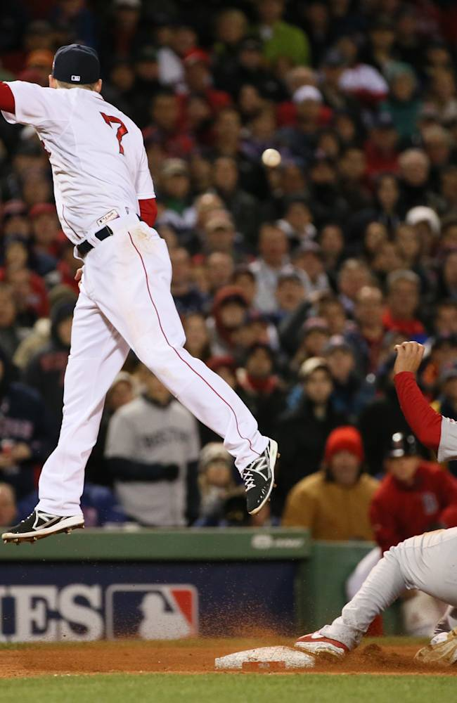 Boston Red Sox shortstop Stephen Drew is unable to catch the errant throw from pitcher Craig Breslow as St. Louis Cardinals' Jon Jay reaches third safely on a Matt Carpenter sacrifice fly in the seventh inning during Game 2 of the World Series between the St. Louis Cardinals and the Boston Red Sox on Thursday, Oct. 24, 2013, at Fenway Park in Boston.  Jay scored on the error