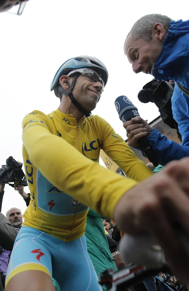 Italy's Vincenzo Nibali, wearing the overall leader's yellow jersey, is interviewed prior to the start of the sixth stage of the Tour de France cycling race over 194 kilometers (120.5 miles) with start in Arras and finish in Reims, France, Thursday, July 10, 2014