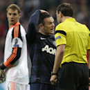 Bayern goalkeeper Manuel Neuer, left, looks around as Manchester United's Wayne Rooney speaks to referee Jonas Eriksson during the Champions League quarterfinal second leg soccer match between Bayern Munich and Manchester United in the Allianz Arena in Mu