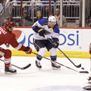 St Louis Blues' Derek Roy (12) skates the puck in on Phoenix Coyotes goaltender Mike Smith, right, as Keith Yandle (3) and Mikkel Boedker, of Denmark, left, defend during the first period of an NHL hockey game, Sunday, March. 2, 2014, in Glendale, Ariz Th