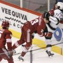Los Angeles Kings' Jordan Nolan (71) battles Arizona Coyotes' Oliver Ekman-Larsson (23) as Coyotes' Andrew Campbell (45) arrives to get in the mix during the second period of a preseason NHL hockey game Monday, Sept. 22, 2014, in Glendale, Ariz. (AP Photo/Ross D. Franklin)