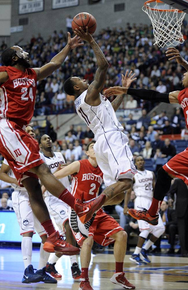 Connecticut's Ryan Boatright (11) drives past Boston University's Travis Robinson (24) and Maurice Watson Jr. (1) during the first half of an NCAA college basketball game in Storrs, Conn., on Sunday, Nov. 17, 2013