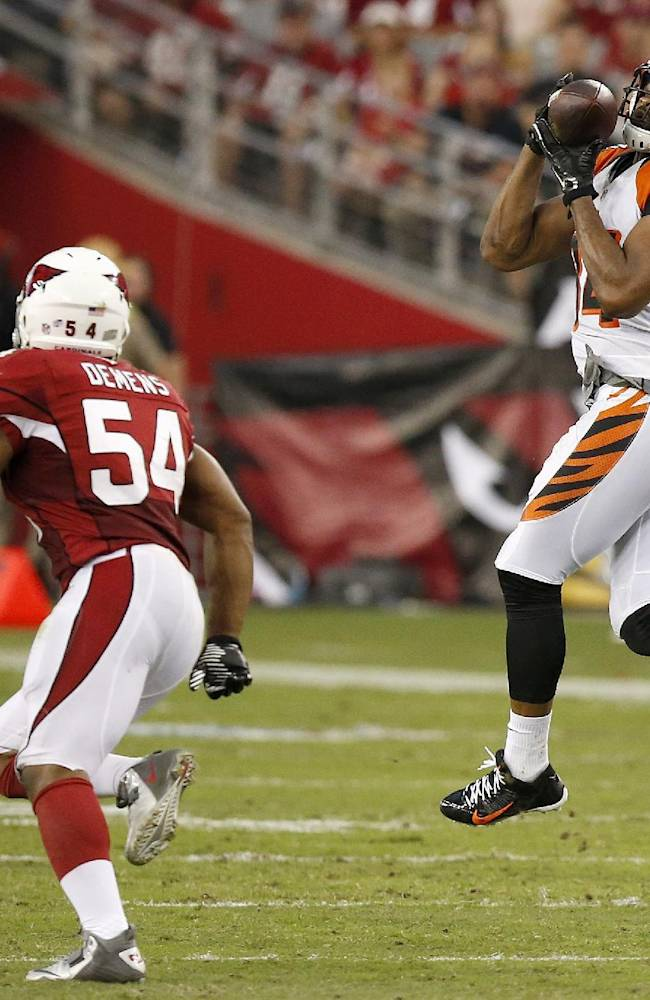 Cincinnati Bengals' Jermaine Gresham, right, makes a jumping catch in front of Arizona Cardinals' Kenny Demens (54) during the first half of an NFL preseason football game Sunday, Aug. 24, 2014, in Glendale, Ariz
