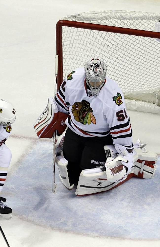St. Louis Blues' Jaden Schwartz, top left, watches as his shot slips past Chicago Blackhawks goalie Corey Crawford and Johnny Oduya (27), of Sweden, for a goal during the third period in Game 1 of a first-round NHL hockey Stanley Cup playoff series Thursday, April 17, 2014, in St. Louis
