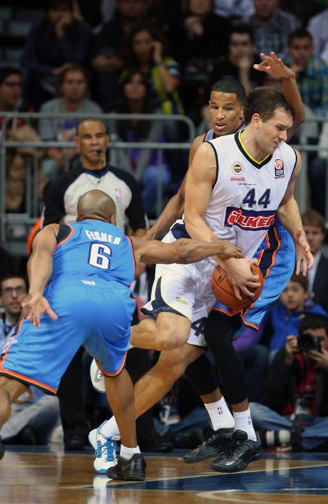 The NBA team Oklahoma City Thunder's Derek Fisher, left, and Andre Roberson, rear,  fight for the ball during with Fenerbahce Ulker's Bojan Bogdanovic during a preseason basketball game in Istanbul, Turkey, Saturday, Oct. 5, 2-13. Oklahoma City Thunder has opened the preseason schedule with a game against the five-time Turkish champions at the Ulker Sports Arena.(AP Photo)