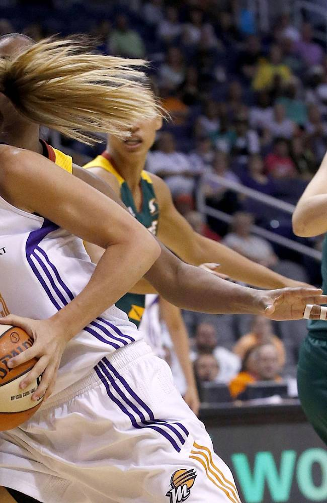Phoenix Mercury's Penny Taylor (13), of Australia, beats Seattle Storm's Sue Bird, right, Camille Little, back left, and Nicole Powell to the basket to get off a shot during the second half of a WNBA basketball game on Tuesday, June 3, 2014, in Phoenix. The Mercury defeated the Storm 87-72