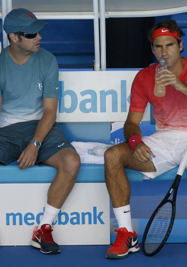 Roger Federer, right, of Switzerland sits with coach  Severin Luethi during a practice session ahead of the Australian Open tennis championship in Melbourne, Australia, Sunday, Jan. 12, 2014