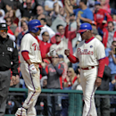 Philadelphia Phillies' Ben Revere, front left, celebrates with first base coach Juan Samuel after hitting a one-run single against the Atlanta Braves in the eight inning of a baseball game on Thursday, April 17, 2014, in Philadelphia. The Phillies won 1-0