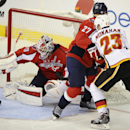 Washington Capitals goalie Braden Holtby (70) reaches for the puck against Calgary Flames center Sean Monahan (23) during the third period of an NHL hockey game, Tuesday, Nov. 4, 2014, in Washington. The Flames won 4-3 in overtime. also seen is Washington