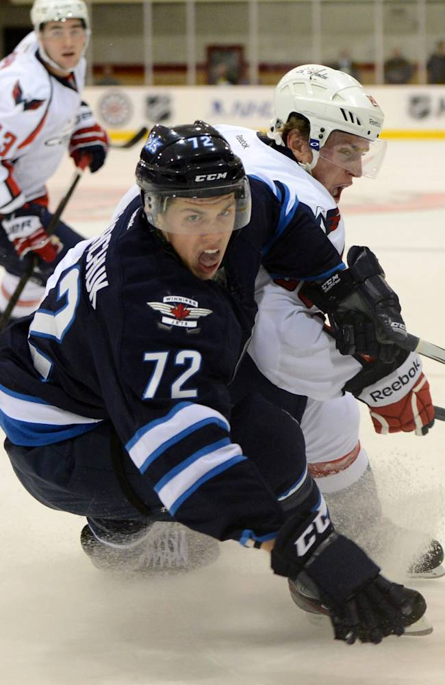 Washington Capitals' Nate Schmidt pushes against Winnipeg Jets' Scott Kosmachuk, foreground, during a preseason NHL hockey game on Saturday, Sept. 14, 2013, in Belleville, Ontario