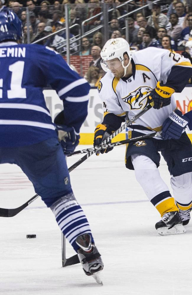 Nashville Predators' Patric Hornqvist,  center, battles for the puck with Toronto Maple Leafs' Jay McClement (11) as Leafs' Nikolai Kulemin covers during the third period of an NHL hockey game, Thursday, Nov. 21, 2013 in Toronto