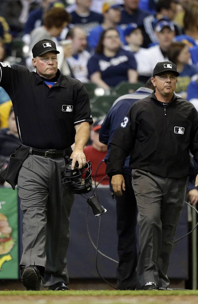 Umpire Ted Barrett, left, signals an out call after listening to the central replay booth in New York in the sixth inning of an opening day baseball game between the Atlanta Braves and Milwaukee Brewers, Monday, March 31, 2014, in Milwaukee. An umpire's call has been overturned for the first time under Major League Baseball's expanded replay system, with Brewers' Ryan Braun ruled out instead of safe