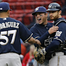 Milwaukee Brewers second baseman Scooter Gennett, middle, celebrates with catcher Jonathan Lucroy, right, and relief pitcher Francisco Rodriguez (57) after they defeated the Boston Red Sox 6-2 in a baseball game at Fenway Park in Boston, Friday, April 4,