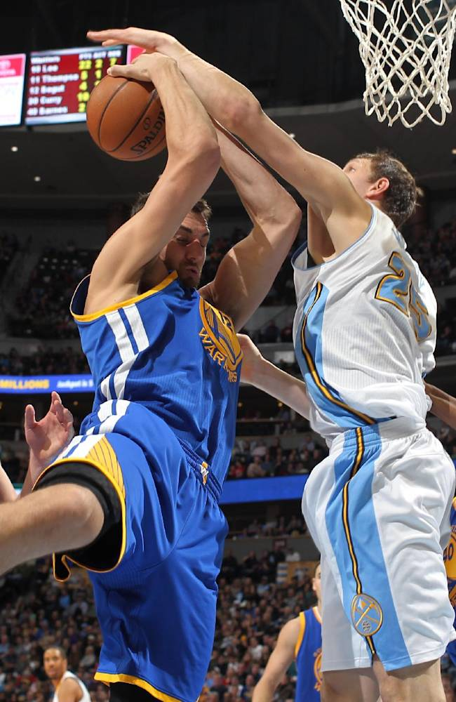 Golden State Warriors center Andrew Bogut, left, of Australia, battles for control of a reobund with Denver Nuggets center Timofey Mozgov, of Russia, in the fourth quarter of the Warriors' 89-81 victory in an NBA basketball game in Denver on Monday, Dec. 23, 2013