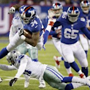 New York Giants running back Brandon Jacobs (34) leaps over Dallas Cowboys strong safety J.J. Wilcox, bottom, during the second half of an NFL football game, Sunday, Nov. 24, 2013, in East Rutherford, N.J The Associated Press