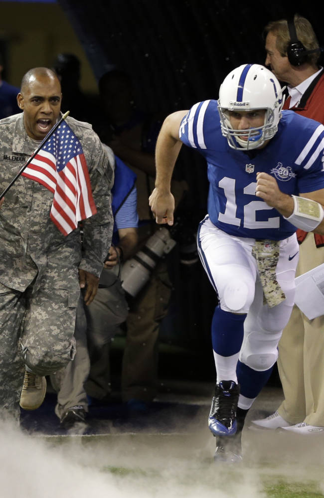Indianapolis Colts quarterback Andrew Luck, right, along with a member of the military is introduced before an NFL football game against the St. Louis Rams as part of the NFL's Salute to Service in Indianapolis, Sunday, Nov. 10, 2013
