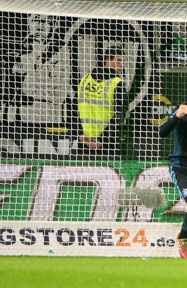 In this picture taken Friday Nov. 29, 2013, Wolfsburg's goalie  Diego Benaglio  sits on the pitch as Hamburg's Pierre-Michel Lasogga, left, celebrates a goal, during the German Bundesliga soccer match between VfL Wolfsburg and Hamburger SV, in Wolfsburg, Germany